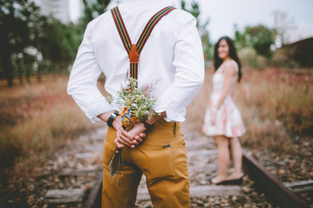 a man wearing suspenders holds flowers behind his back - a woman in a white dress looks over smiling - both standing on railroad tracks.