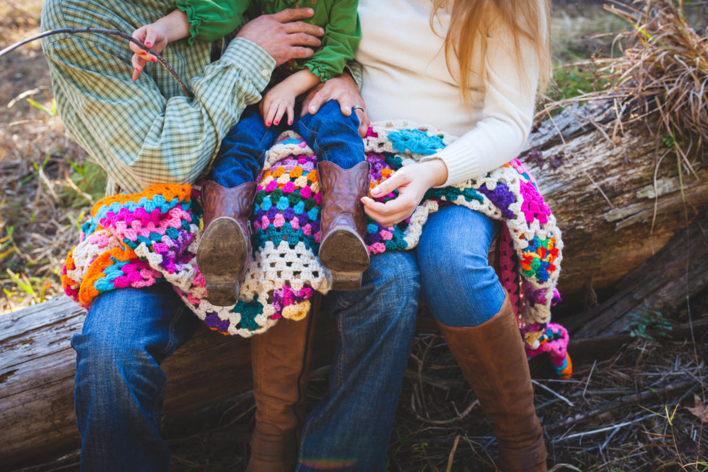 man and woman holding a child on a colorful, crocheted blanket
