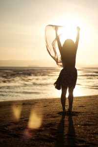 a woman in silhouette with arms raised looking out at the ocean