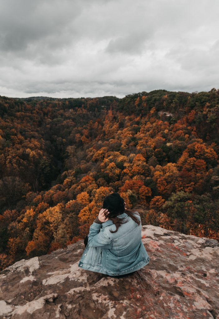 woman in a denim jacket sitting on a mountain rock looking out over autumn trees