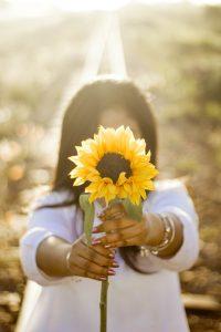 girl wearing white holding sunflower