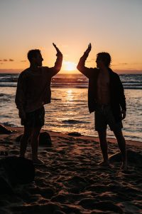two people doing a high-five on the beach in silhouette
