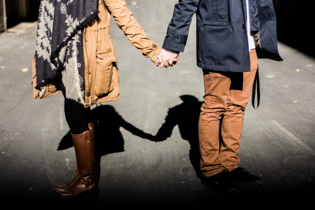 a couple standing, holding hands, shadows behind them