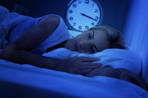 woman lying in bed, 3:17 showing on the analog clock
