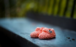 salmon-colored crocheted baby boots