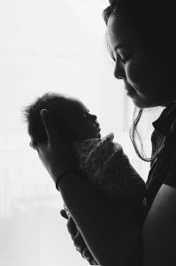 a mother holding a newborn baby, black & white photo