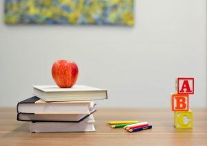 an apple sitting on top of four books, colored pencils, and three blocks reading A, B, and C on a tabletop
