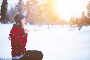 woman sitting quietly in a meditation pose in the snow