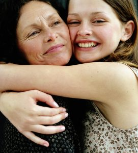 tween girl hugging her mom, both smiling