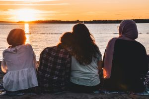 four friends sitting on the shore watching the sun set over water, two in the middle sitting close