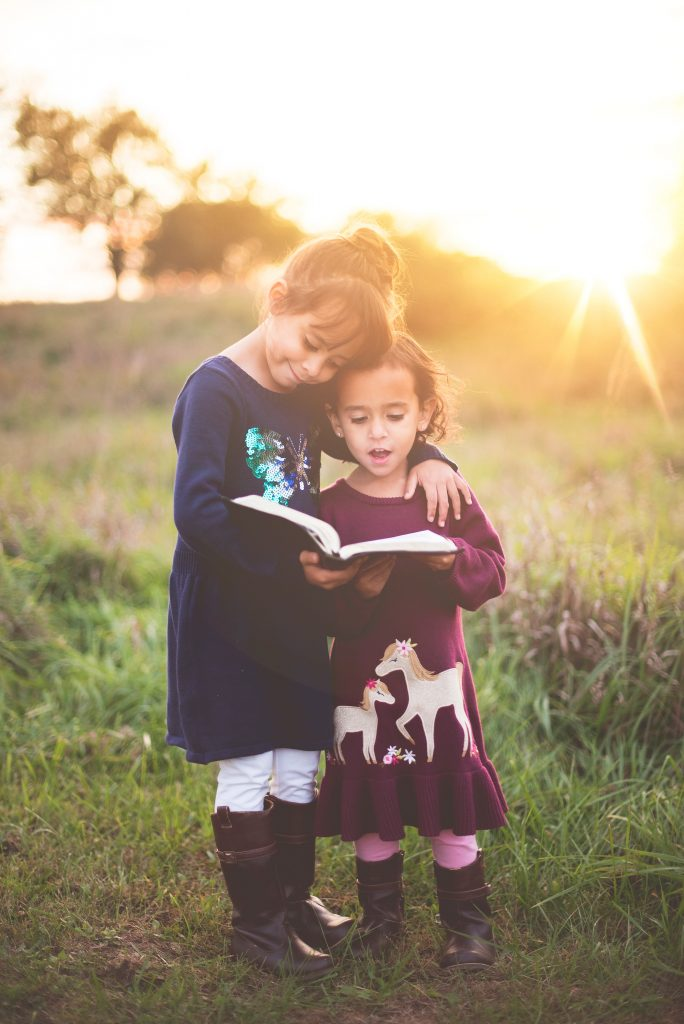 two little girls standing in a meadow and reading