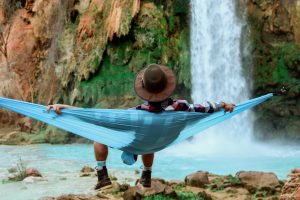person relaxing in a hammock by a waterfall