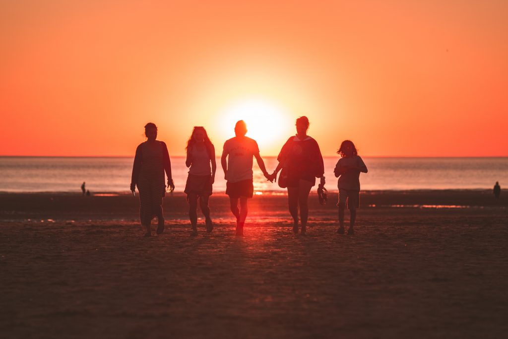 five people walking on a beach at sunset, two of them holding hands