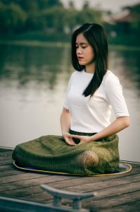 a woman with long, dark hair sitting on a dock in a Zen meditation pose