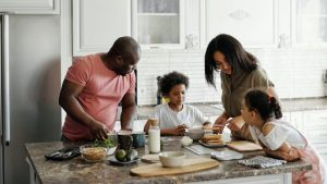 four person family making breakfast together at the kitchen table