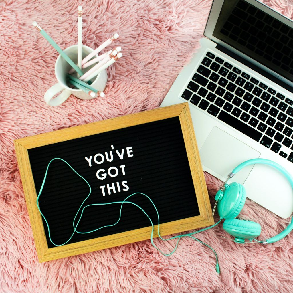 """a mug holding pencils, a laptop, lime green headphones, and a framed message that says """"YOU'VE GOT THIS"""" arranged on a pink shag carpet"""