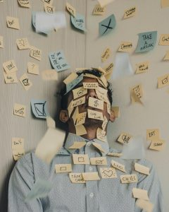 a man standing against a wall with post-it notes all over his face, shirt, and the wall behind him