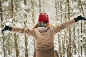 a woman dressed for winter standing in a snowy forest, arms outstretched