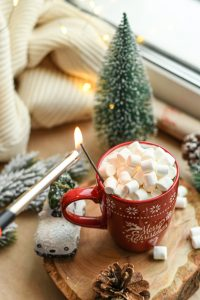 holiday display with evergreen, pine cones, and hot chocolate with marshmallows candle