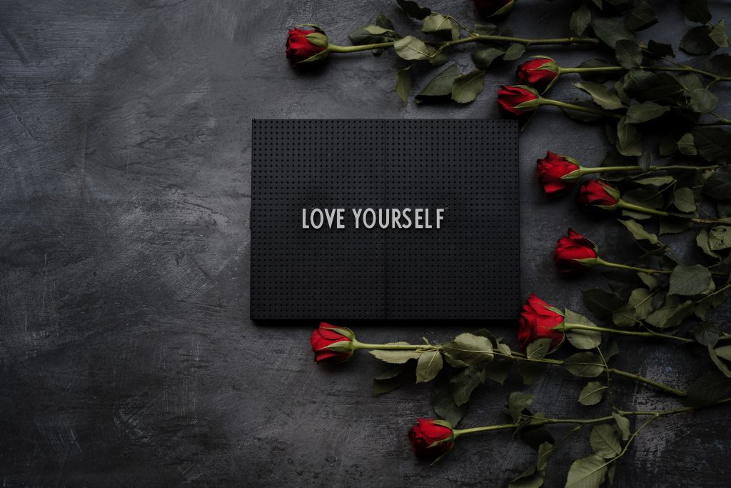 """white letters on a black rectangular card which reads """"LOVE YOURSELF"""" encircled by red long stem roses"""