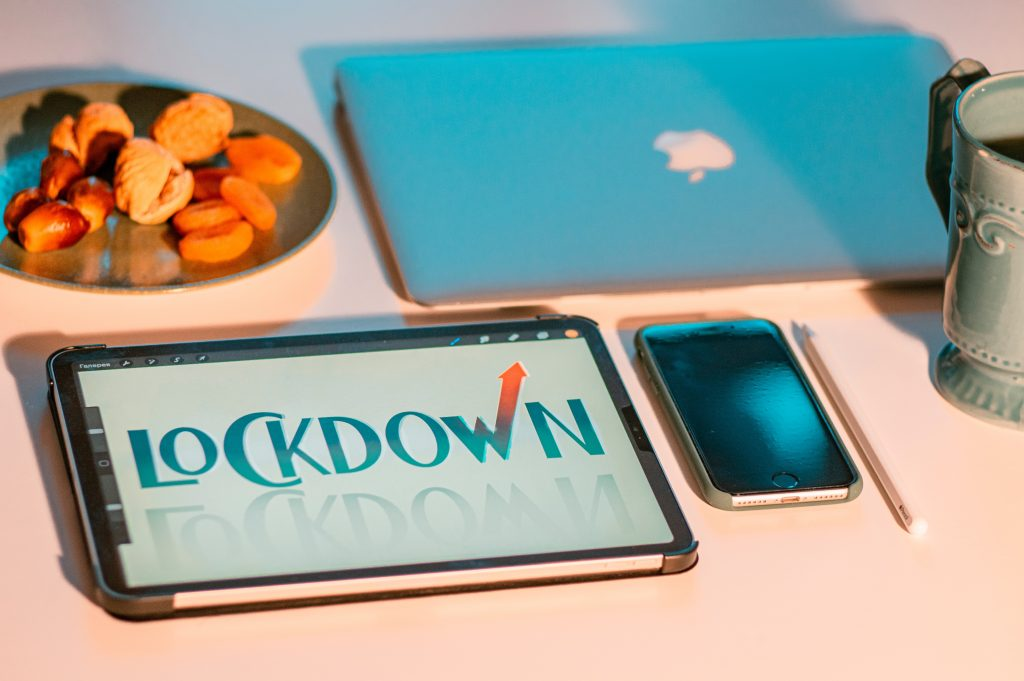 """a plate of fruit and nut snacks, a laptop, cell phone, ceramic mug, pencil, and tablet showing a """"LOCKDOWN"""" graphic"""