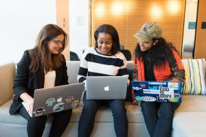 three women sitting on a couch looking at their laptops