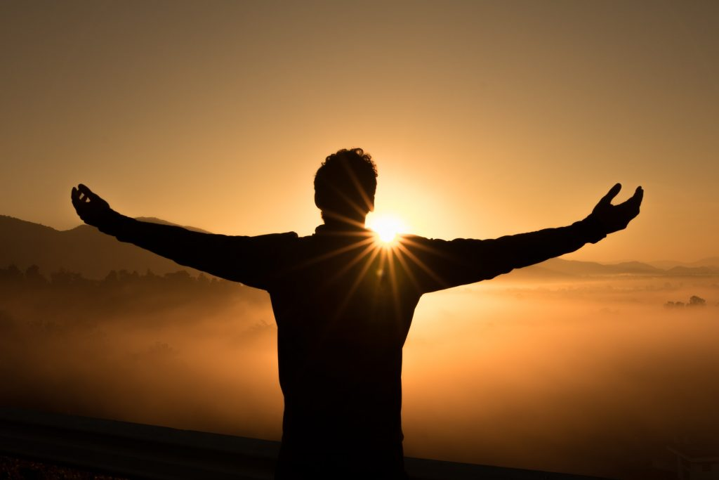person with outstretched arms facing the sun as it sets